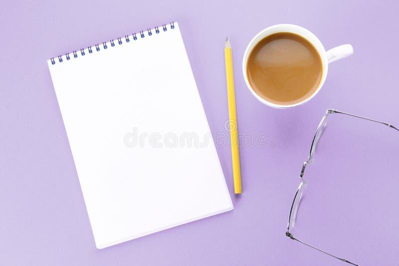 La imagen de la visión superior del cuaderno abierto con las páginas en blanco y el café en fondo azul, alista para añadir o imit foto de archivo libre de regalías