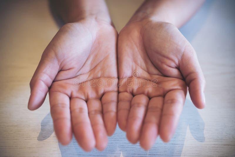La imagen de la visión superior de la mujer abre la palma de las manos con la tabla de madera blanca foto de archivo libre de regalías