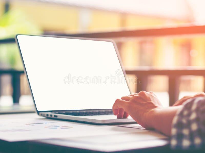 La imagen de la vista posterior de la mano de la mujer de negocios usando el ordenador portátil en la tabla de madera con el espa fotos de archivo libres de regalías