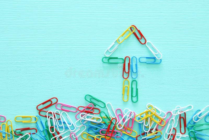 La imagen del concepto de la creatividad o piensa fuera de la caja paperclips que forman una flecha, un trabajo en equipo y un di imagen de archivo libre de regalías