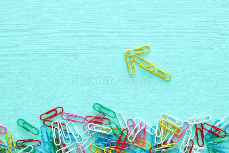La imagen del concepto de la creatividad o piensa fuera de la caja paperclips que forman una flecha, un trabajo en equipo y un di fotos de archivo libres de regalías