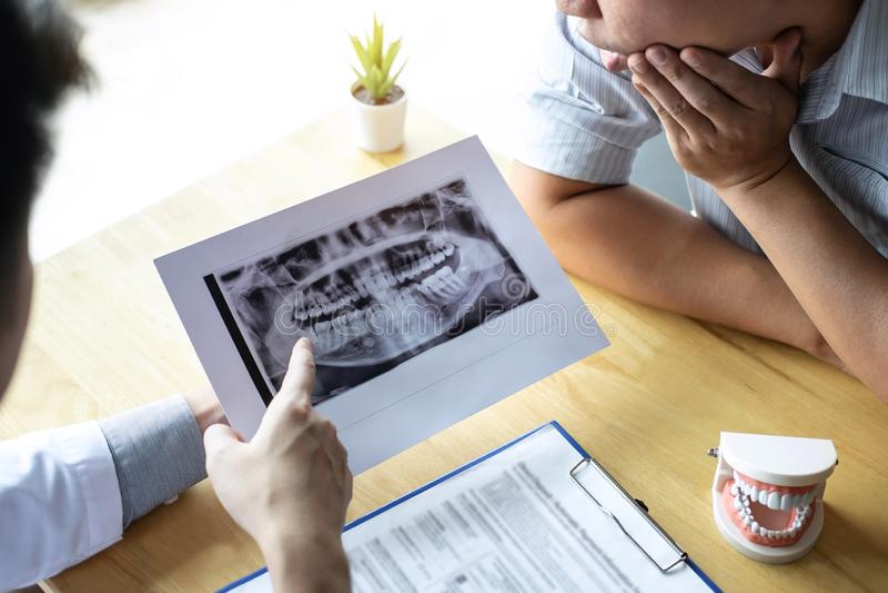 La imagen del doctor o el dentista que presenta con la película de radiografía del diente recomienda paciente en el tratamiento d imagen de archivo libre de regalías