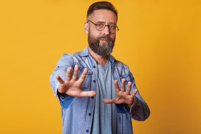 La imagen del gesto envejecido medio atractivo de la denegación de la demostración del hombre, tiene expresión facial seria, chaq imagen de archivo libre de regalías