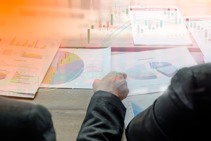 La imagen del hombre de negocios dos discute el documento del informe de la carta de la venta sobre la tabla foto de archivo