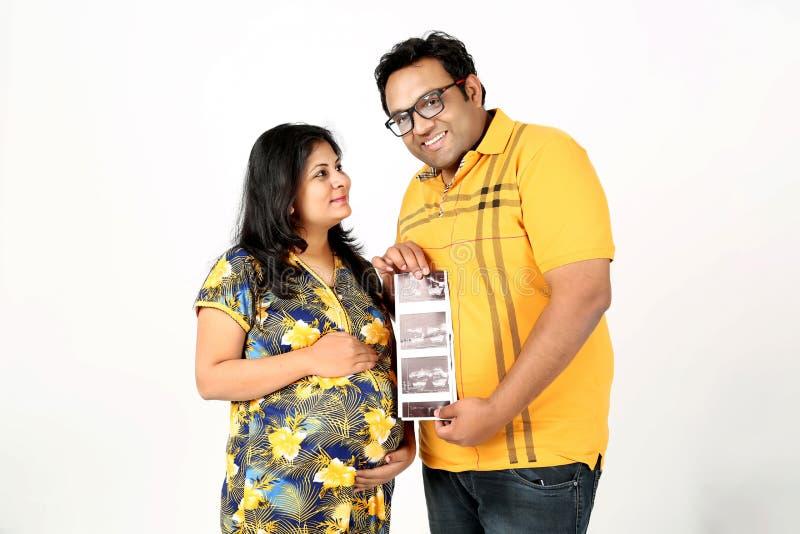 La imagen del hombre está llevando a cabo ultrasonido a disposición con la esposa embarazada fotos de archivo