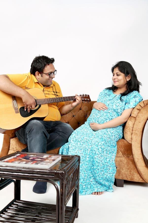 La imagen del hombre está tocando la guitarra a su esposa embarazada imagenes de archivo