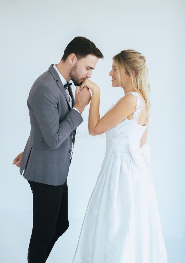 La imagen del novio con los pares rom?nticos de la novia se est? besando junta en el fondo blanco, pensamiento positivo en d?a de fotografía de archivo libre de regalías