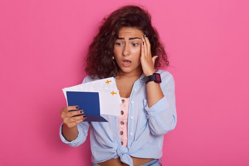 La imagen del pasaporte confuso de la tenencia de la mujer con los boletos, mirando documentos con la expresión facial trastornad imagen de archivo