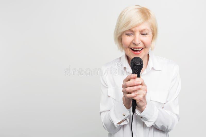 La imagen hermosa y blanda de la mujer madura impresionante que cantaba a una canción con ella ojos se cerró usando un micrófono  foto de archivo