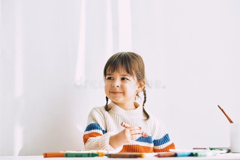 La imagen horizontal de la niña linda feliz pinta con los lápices del aceite, sentándose en el escritorio blanco en casa imagen de archivo