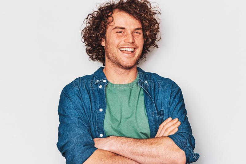 La imagen horizontal del estudio del hombre sonriente que presenta para el anuncio lleva la camisa azul, cruzó sus manos, aislada fotografía de archivo