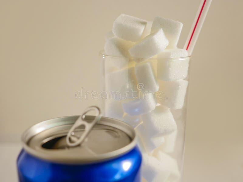 La imagen inmóvil conceptual de la vida del vidrio con los cubos llenos del azúcar de la paja y la soda restauran la bebida en el foto de archivo