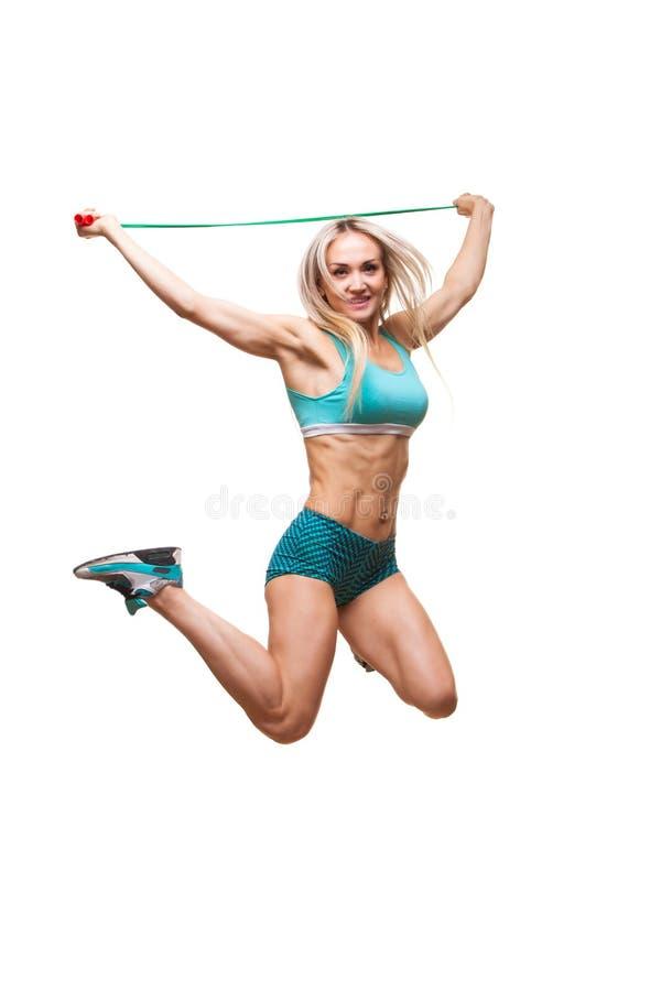 La imagen integral de un joven se divierte a la mujer que salta en cuerda que salta sobre el fondo blanco foto de archivo