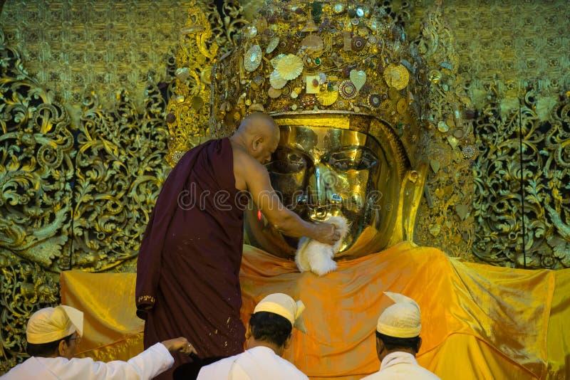La imagen mayor de Mahamuni Buda del lavado del monje en el ritual del lavado de la cara de la imagen de Buda cada mañana en 4am fotografía de archivo libre de regalías