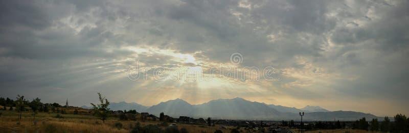 La imagen panorámica de la salida del sol de mirada dramática del cielo con rayos solares o ángel irradia con Rocky Mountains a l imagenes de archivo