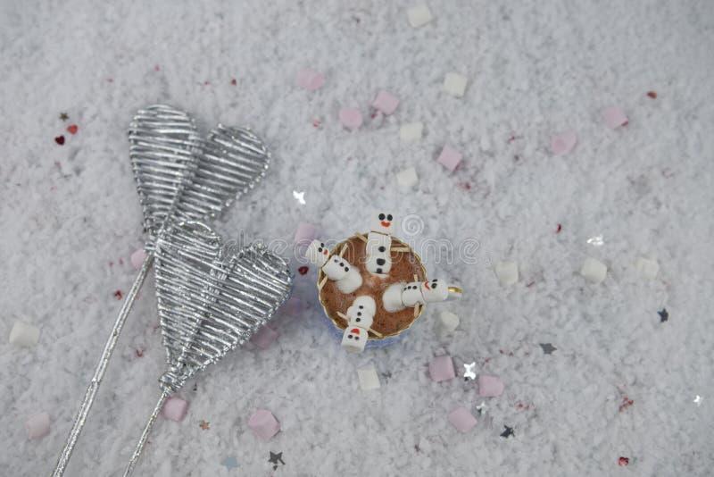 La imagen romántica de la fotografía del invierno con la bebida del chocolate caliente y las mini melcochas formadas como muñeco  imágenes de archivo libres de regalías