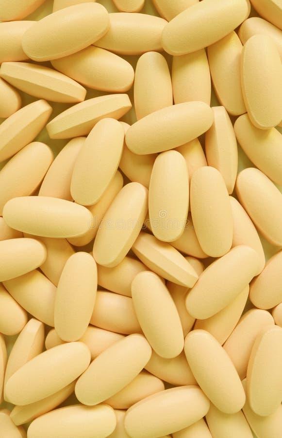 La imagen vertical del montón del óvalo amarillo cremoso formó píldoras del suplemento imágenes de archivo libres de regalías