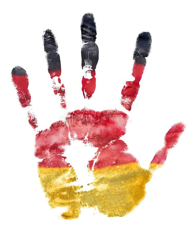 La impresión de la mano izquierda en los colores de la bandera alemana fotografía de archivo