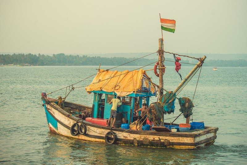 La India, Goa - 2 de febrero de 2017: Un barco de pesca con una bandera del indio navega en el mar fotografía de archivo