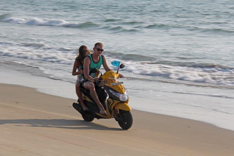 La India, GOA, el 22 de enero de 2018 Una muchacha y un individuo están montando una vespa a lo largo de la costa Scooter on the  imagen de archivo libre de regalías