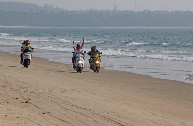 La India, GOA, el 22 de enero de 2018 Una muchacha y un individuo están montando una vespa a lo largo de la costa Scooter on the  imagenes de archivo