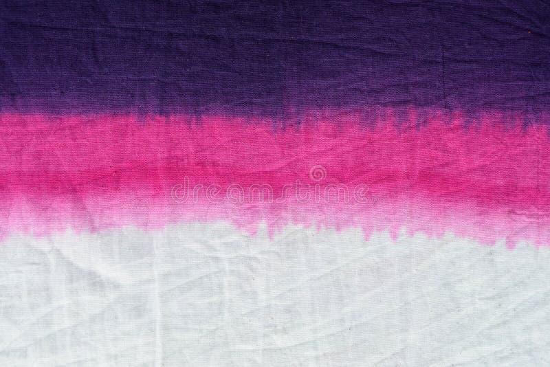 La inmersión rosada del modelo del teñido anudado del tono teñió técnica en fondo de la tela de algodón fotos de archivo