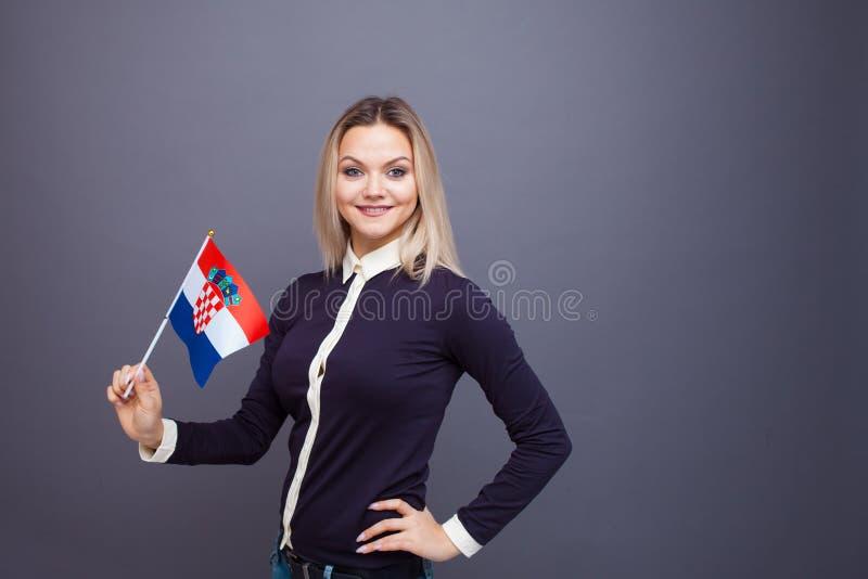La inmigración y el estudio de los idiomas extranjeros, concepto Una joven sonriente con una bandera croata en la mano fotografía de archivo libre de regalías