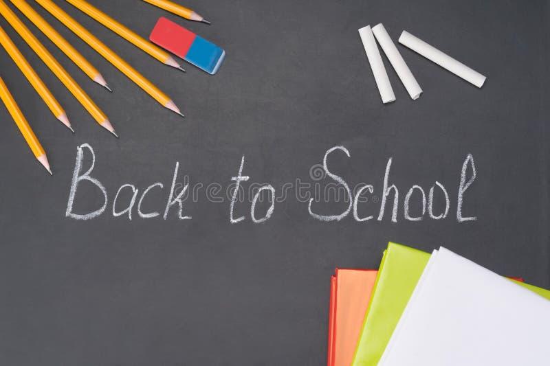 La inscripción 'de nuevo a escuela 'se escribe en tiza en una pizarra entre los efectos de escritorio imagen de archivo