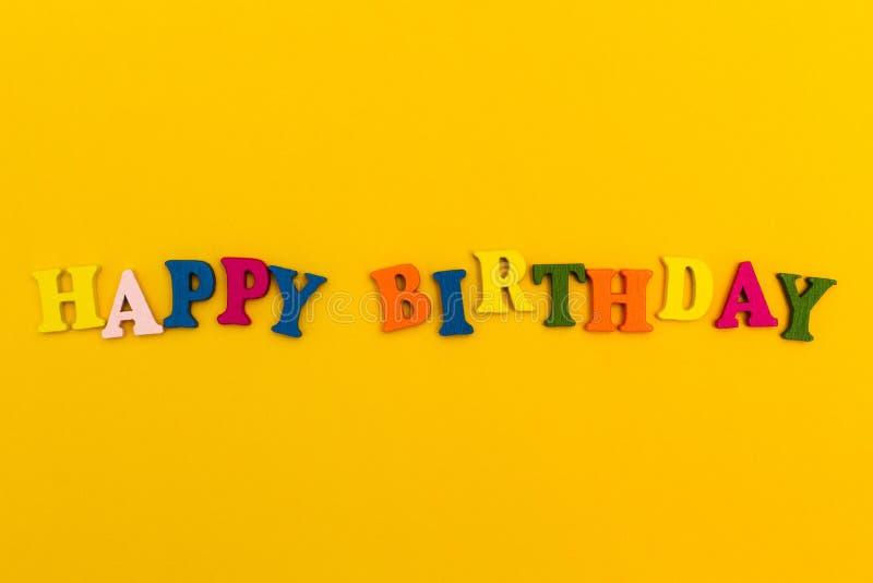 La inscripción 'feliz cumpleaños 'en letras coloridas en un fondo amarillo imagen de archivo libre de regalías