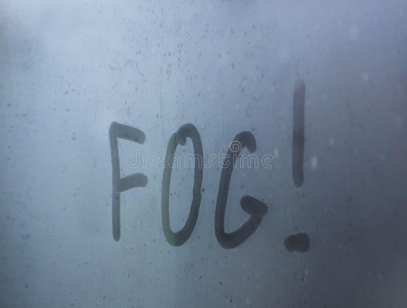 La inscripción - 'niebla 'escrita por un finger en un vidrio misted con descensos del mkrymi Motoristas de cuidado sobre los peli foto de archivo