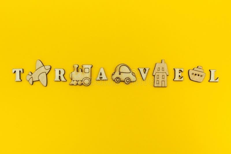 La inscripción 'viaje 'se mezcla con las figuras de madera del aeroplano, del tren, de la nave, del coche y del hotel fotos de archivo libres de regalías