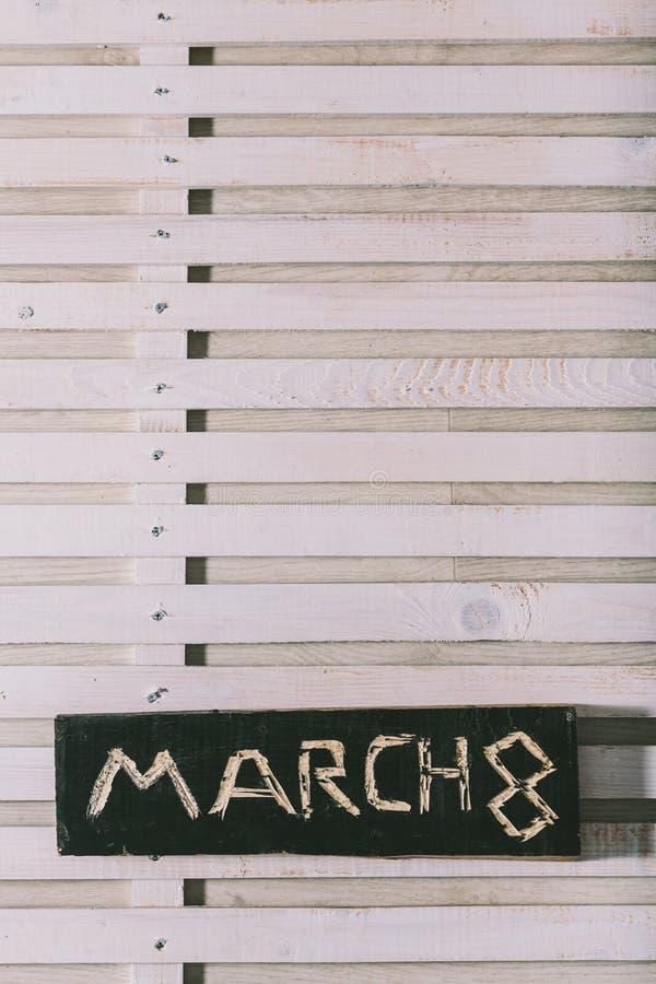 La inscripción el 8 de marzo se corta en un tablero de madera negro grange fotografía de archivo libre de regalías