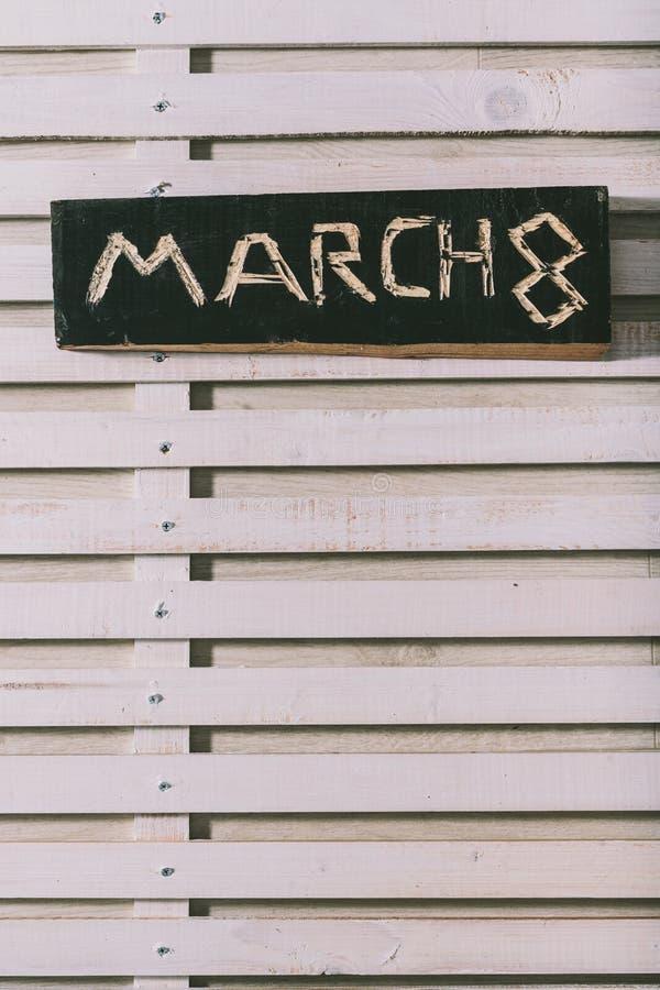 La inscripción el 8 de marzo se corta en un tablero de madera negro grange imagenes de archivo