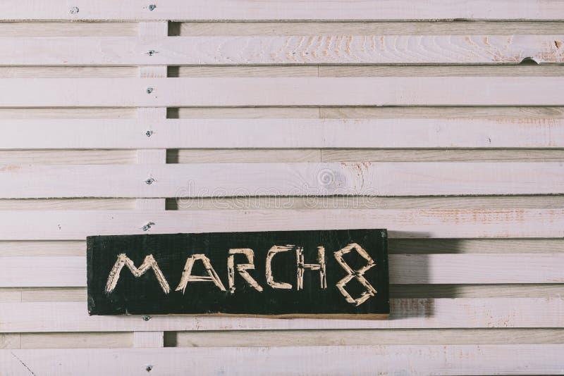 La inscripción ` el ` del 8 de marzo se corta en un tablero de madera negro grange imágenes de archivo libres de regalías