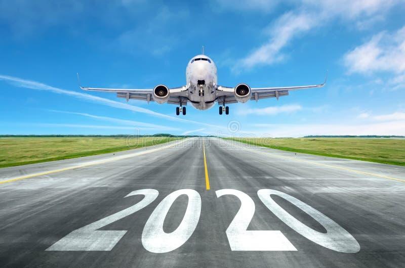 La inscripción en la pista 2020 de la pista de aterrizaje del aeropuerto con despegue aéreo Concepto de viaje en el nuevo año, imagenes de archivo