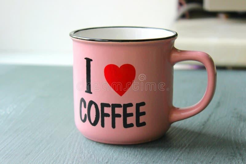 La inscripci?n ?amo el caf? ?en una taza rosada rodeada por los granos de caf? copie el espacio para su texto foto de archivo libre de regalías