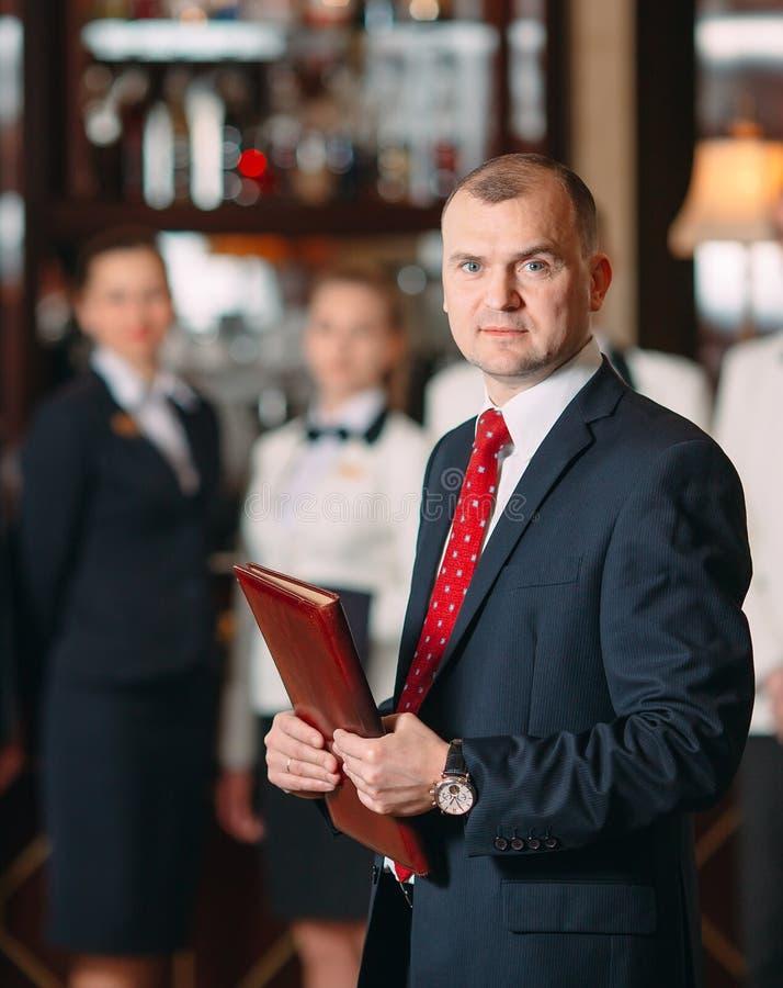 La interacci?n del personal Encargado del hotel o del restaurante y su personal en cocina el obrar recíprocamente al chef adentro fotografía de archivo libre de regalías