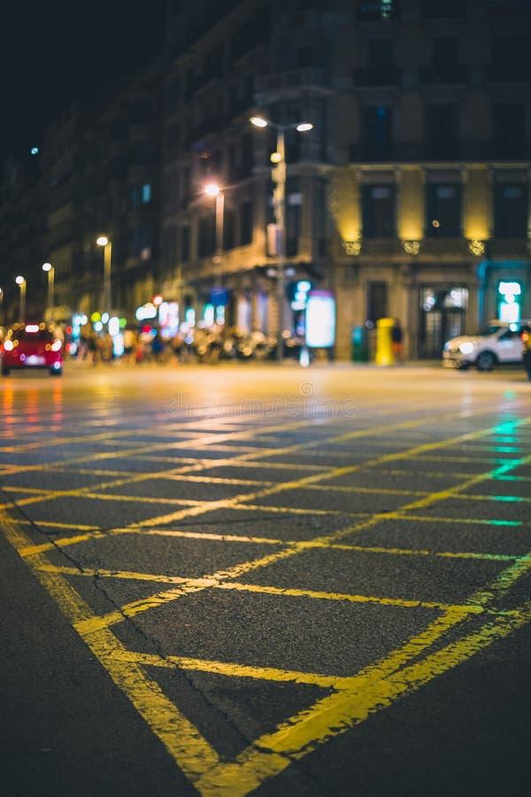 La intersección de las calles pintó en amarillo en la ciudad durante noche imagen de archivo libre de regalías