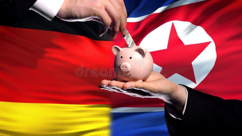 La inversión de Alemania en Corea del Norte, mano pone el dinero en el piggybank, fondo de la bandera imagenes de archivo