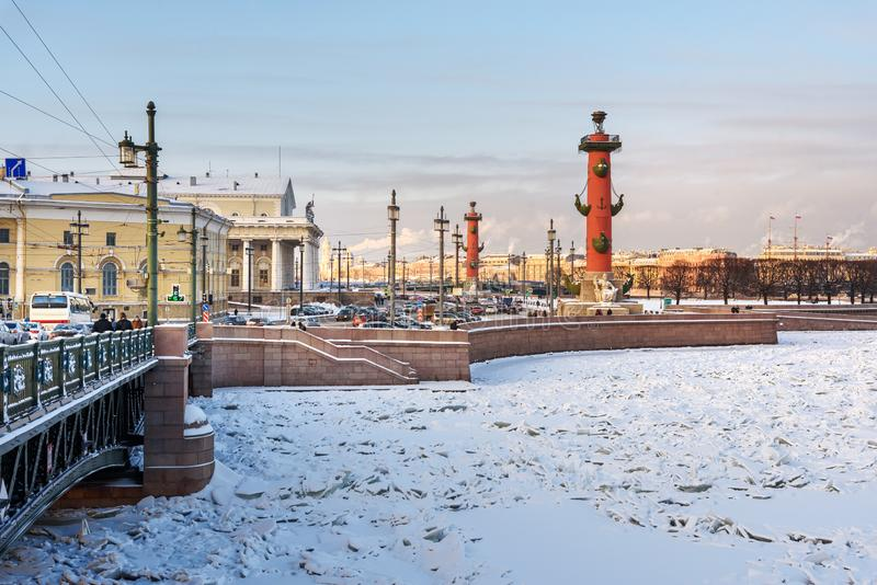 La isla del puente y de Vasilyevsky del palacio escupe Strelka con las columnas rostrales en invierno St Petersburg, Rusia fotos de archivo