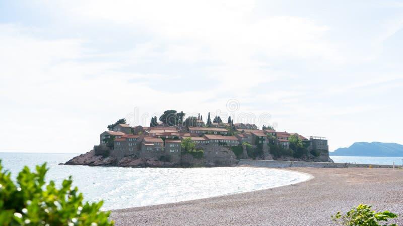 La isla hist?rica y el para?so de la ciudad de Sveti Stefan enarenan la playa Budva, Montenegro Hotel en una pequeña roca en el m imagen de archivo