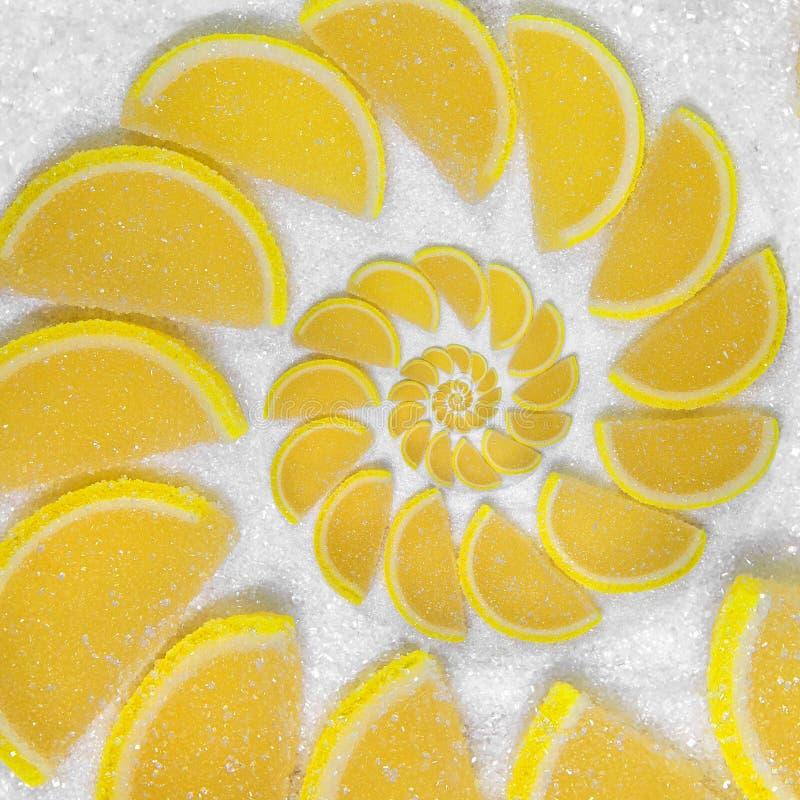 La jalea de fruta abstracta acuña el lóbulo amarillo del pedazo en fondo del azúcar blanco Jaleas amarillas Segmentos dulces de l foto de archivo libre de regalías
