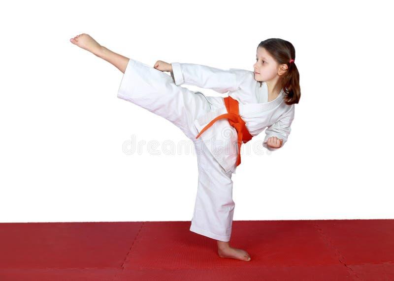 La jambe élevée donnent un coup de pied de petits athlètes dedans exécutés image stock