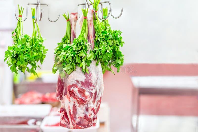 La jambe crue entière d'agneau a accroché sur le crochet avec le groupe de persil au marché ou à la boutique Viande préparée pour image libre de droits