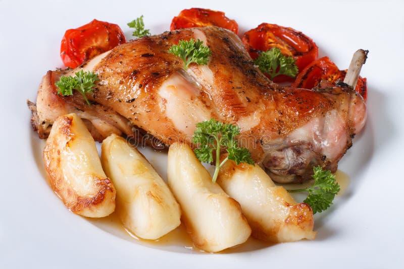 La jambe de lapin a rôti avec des pommes et des tomates sur un plan rapproché de plat image stock