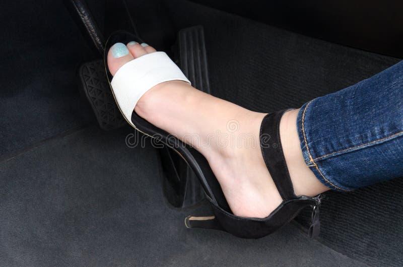 La jambe des femmes sur la pédale de voiture photos libres de droits