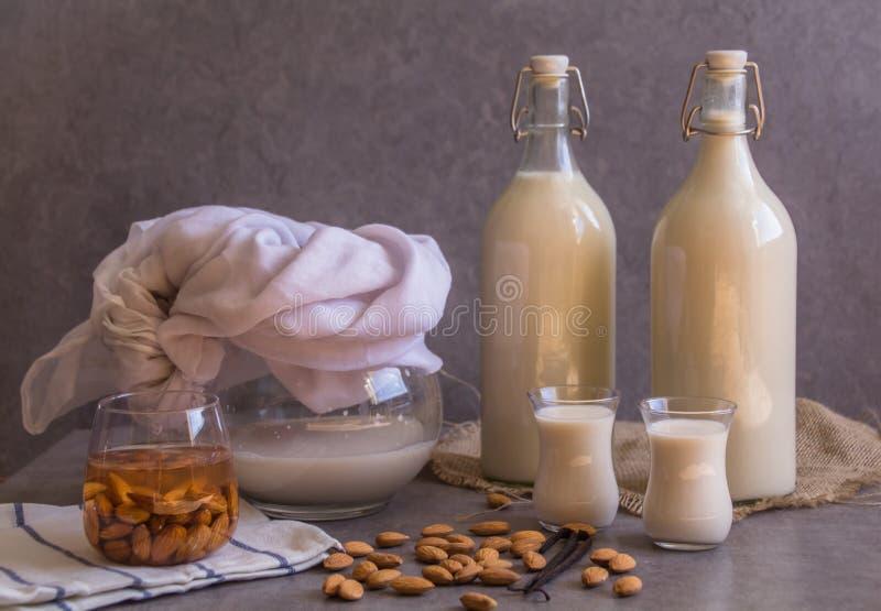 La jarra, dos botellas y dos pequeños vidrios llenados de leche hecha en casa de la almendra en fondo gris rústico, nueces crudas imagen de archivo