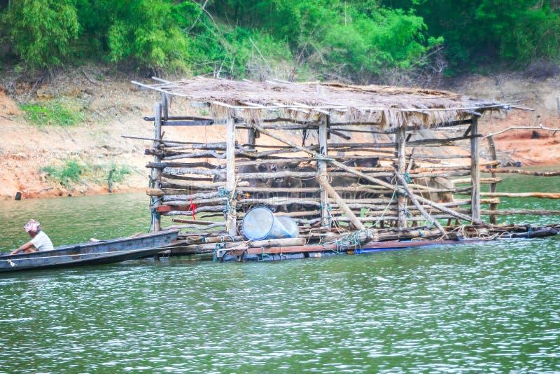La jaula de madera de la balsa y tiene búfalo dentro, arrastrando por un barco de la cola larga con el hombre en el río, transp foto de archivo