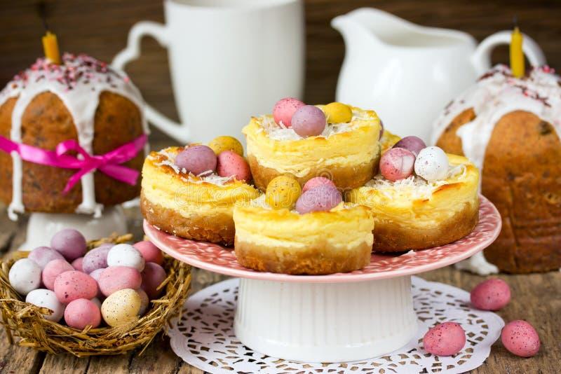 La jerarquía de Pascua apelmaza los pasteles de queso con los huevos de caramelo coloridos de chocolate imagen de archivo libre de regalías