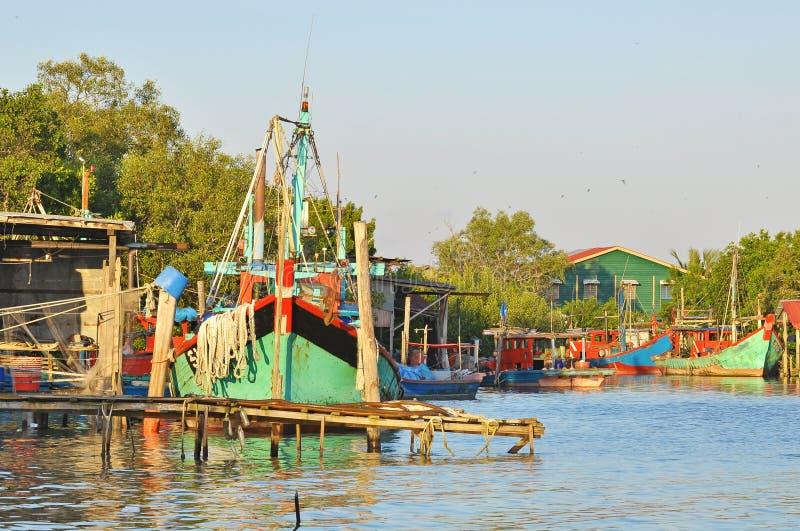La jetée en bois et le bateau profond de pêche maritime s'accouplent à la baie au fishin photos libres de droits